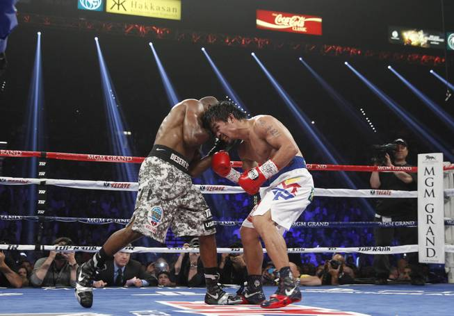 Manny Pacquiao, right, and undefeated WBO welterweight champion Timothy Bradley battle during their title fight at the MGM Grand Garden Arena on Saturday, April 12, 2014.