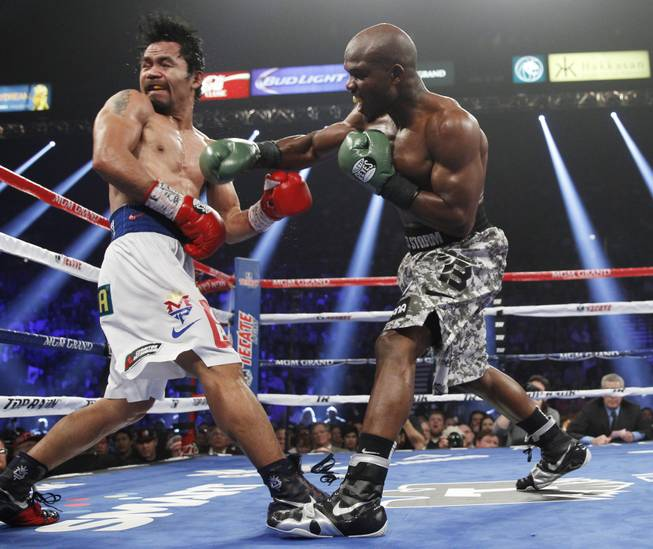 Manny Pacquiao is hit with a right from undefeated WBO welterweight champion Timothy Bradley during their title fight at the MGM Grand Garden Arena on Saturday, April 12, 2014.