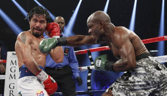 Manny Pacquiao is hit by undefeated WBO welterweight champion Timothy Bradley during their title fight at the MGM Grand Garden Arena on Saturday, April 12, 2014. Pacquiao won by unanimous decision.