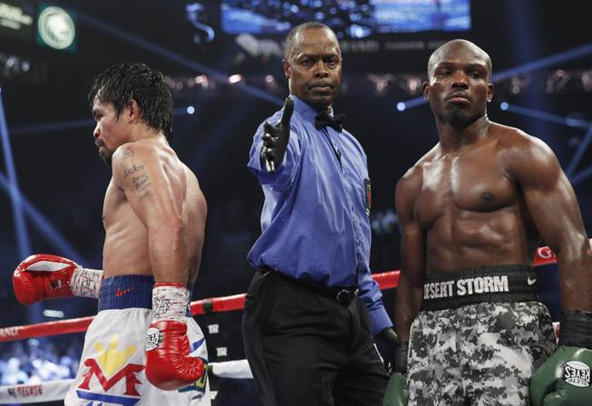 Referee Kenny Bayless separates Manny Pacquiao, left, and undefeated WBO welterweight champion Timothy Bradley at the end of a round of their title fight at the MGM Grand Garden Arena on Saturday, April 12, 2014. Pacquiao won by unanimous decision.