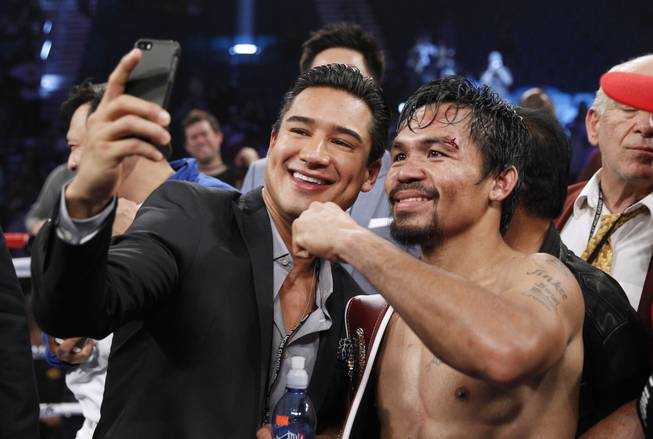 Manny Pacquiao of the Philippines takes a photo with actor Mario Lopez as he celebrates his unanimous decision over WBO welterweight champion Timothy Bradley during their title fight at MGM Grand Garden Arena on Saturday, April 12, 2014. Bradley was previously undefeated.