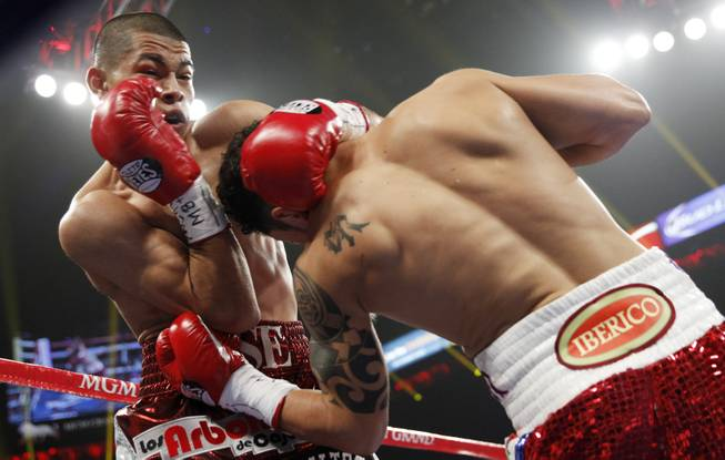 Jose Felix (left) of Mexico is hit with a left by Bryan Vazquez of Costa Rica during their WBA interim super featherweight fight at the MGM Grand Garden Arena on Saturday, April 12, 2014.