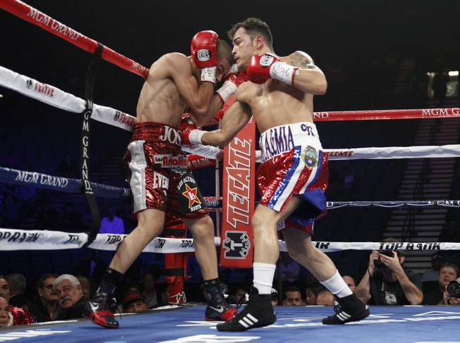 Jose Felix (left) of Mexico is hit by a right from Bryan Vazquez of Costa Rica during their WBA interim super featherweight fight at the MGM Grand Garden Arena on Saturday, April 12, 2014.