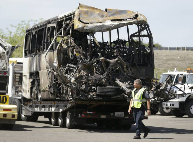 A California Highway Patrol officer walks past the charred remains of a tour bus at a CalTrans maintenance station in Willows, Calif., on Friday, April 11, 2014.