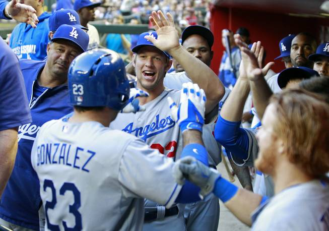 Los Angeles Dodgers' Adrian Gonzalez (23) is congratulated by Clayton Kershaw, center, and other teammates after hitting a two-run home run against the Arizona Diamondbacks during the third inning of a baseball game Saturday, April 12, 2014, in Phoenix.