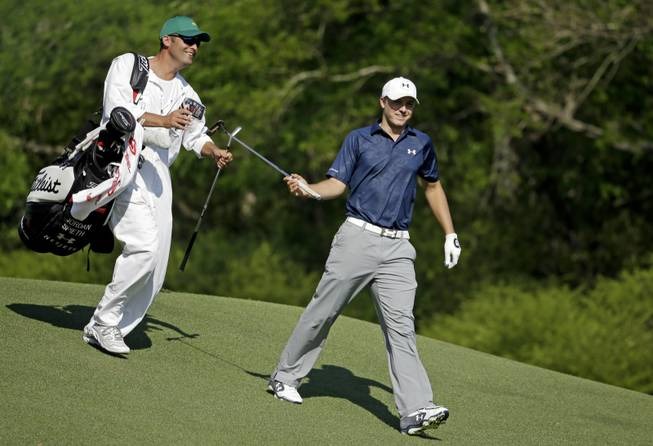 Jordan Spieth gets his putter from caddie Michael Greller after teeing off on the 12th hole during the third round of the Masters golf tournament Saturday, April 12, 2014, in Augusta, Ga.