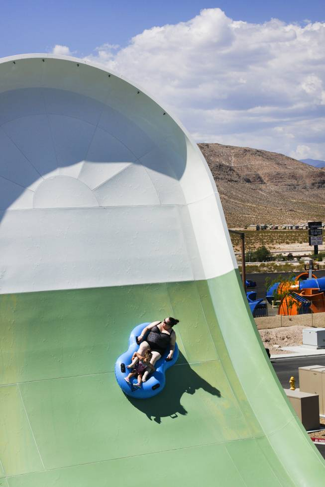 A pair of sliders enjoy the Hoover Half Pipe at Wet 'n' Wild during the first day of its weeklong spring break opening Saturday, April 12, 2014.
