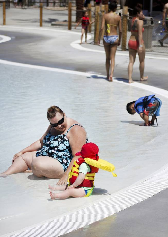 Angie Orozco and her grandson, Silas, foreground, enjoy the wave pool at Wet 'n' Wild during the first day of its weeklong spring break opening Saturday, April 12, 2014.