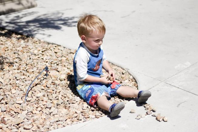 Ammon Glenn, 2, decides to play with the rocks instead of getting wet at the Kiddie Cove at Wet 'n' Wild during the first day of its weeklong spring break opening Saturday, April 12, 2014.