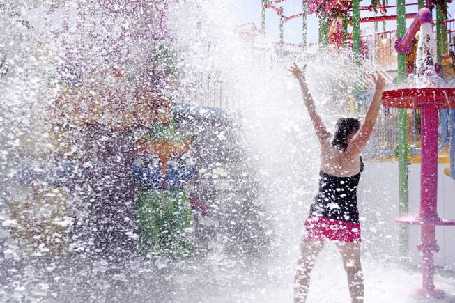 Jaclyn Wehrer gets splashed by the giant water dumping bucket at the Kiddie Cove at Wet 'n' Wild during the first day of its weeklong spring break opening Saturday, April 12, 2014.