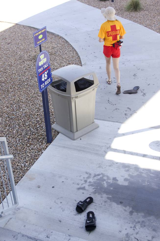 A lifegaurd walks by abondoned flip flops at Wet 'n' Wild during the first day of its weeklong spring break opening Saturday, April 12, 2014.