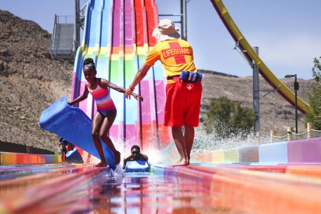 A lifeguard helps a girl get out of the way as a slider reaches the end of the Desert Racer slides at Wet 'n' Wild during the first day of its weeklong spring break opening Saturday, April 12, 2014.