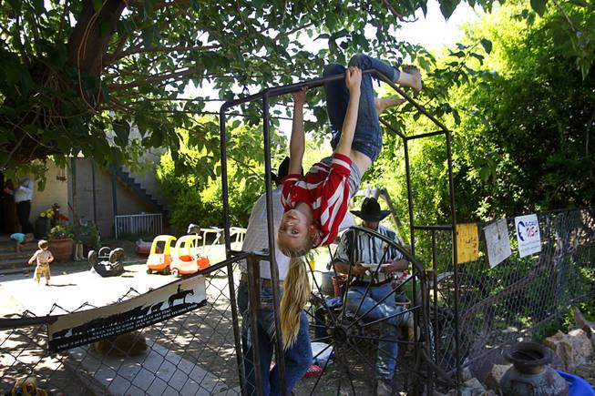 Jerusha Bundy, 10, plays on a gate at the family ranch near Bunkerville Sunday, April 13, 2014. The Bureau of Land Management halted their roundup of Bundy family cattle under an agreement reached Saturday.