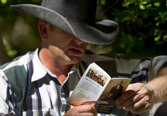 Rayn Bundy, one of Cliven Bundy's sons, reads the U.S. constitution, at the family ranch near Bunkerville Sunday, April 13, 2014. The Bureau of Land Management halted their roundup of Bundy family cattle under an agreement reached Saturday.