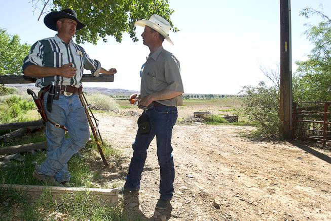 Ryan Bundy, left, one of Cliven Bundy's sons, talks with Wayne Hage near Bunkerville Sunday, April 13, 2014. The Bureau of Land Management halted their roundup of Bundy family cattle under an agreement reached Saturday.