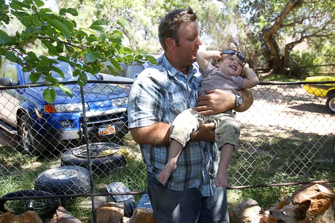 Dave Bundy, one of Cliven Bundy's son's, holds his son Payten, 18-months, at the family ranch near Bunkerville Sunday, April 13, 2014. The BLM halted their roundup of Bundy family cattle under an agreement reached Saturday.
