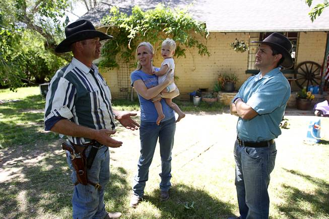 Ryan Bundy, left, one of Cliven Bundy's sons, talks with David Lory VanDerBeek, an Independent American Party candidate for governor, at the family ranch near Bunkerville Sunday, April 13, 2014. Ryan's wife Angela holds their son Moroni, 2, at center.