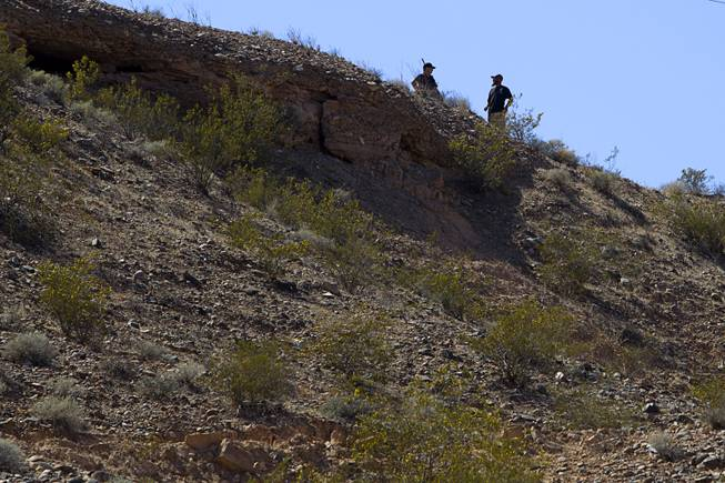 Militia-style volunteers take a position on a hill overlooking a gathering area for Bundy family supporters near Bunkerville Sunday, April 13, 2014. The Bureau of Land Management halted their roundup of Bundy family cattle under an agreement reached Saturday.