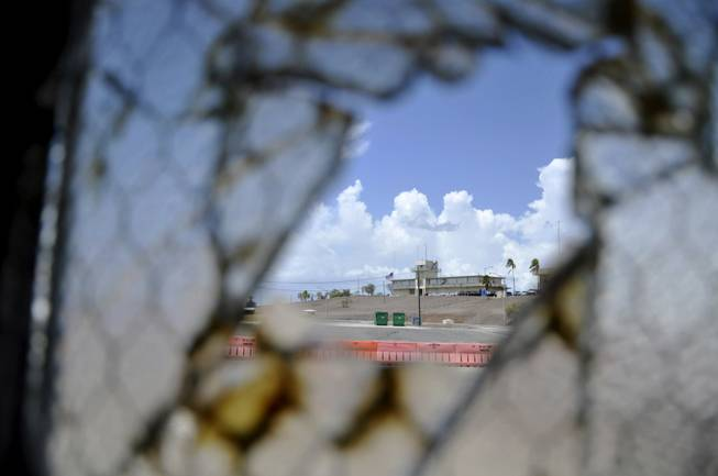 In this Aug. 23, 2013, file photo reviewed by the U.S. Department of Defense, one of Guantanamo Bay's two courthouses is seen through a broken window at Camp Justice at the Guantanamo Bay U.S. Naval Base, Cuba.