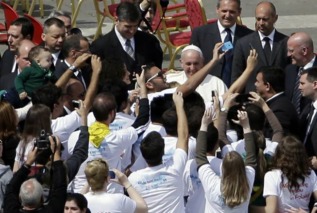"Pope Francis poses for pictures with faithful at the end of a Palm Sunday service in St. Peter's Square, at the Vatican, Sunday, April 13, 2014. Pope Francis, marking Palm Sunday in a packed St. Peter's Square, ignored his prepared homily and spoke entirely off-the-cuff in a remarkable departure from practice. Later, he hopped off his popemobile to pose for ""selfies"" with young people in the crowd. In his homily, Francis called on people, himself included, to look into their own hearts to see how they are living their lives."