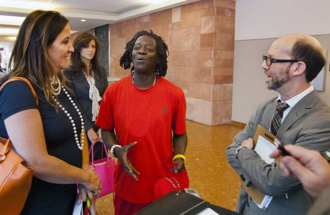 William Jonathan Drayton, Jr., aka Flavor Flav, jokes around with his lawyers Kristina Wildeveld and Dayvid Figler following his appearance before Judge Kathy Hardcastle at the Regional Justice Center on Monday, April 14, 2014.