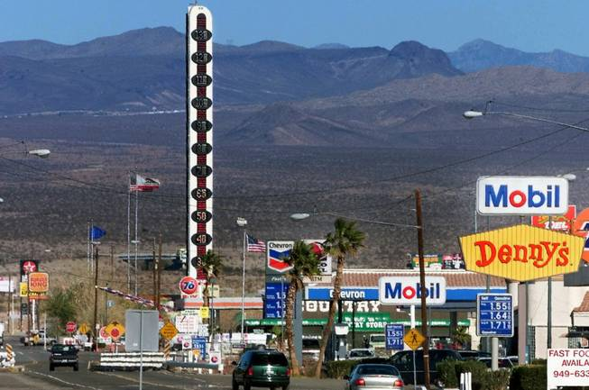 This Jan. 27, 2000, file photo shows visitors driving through the town of Baker, Calif., as the world's tallest thermometer stands in the background.