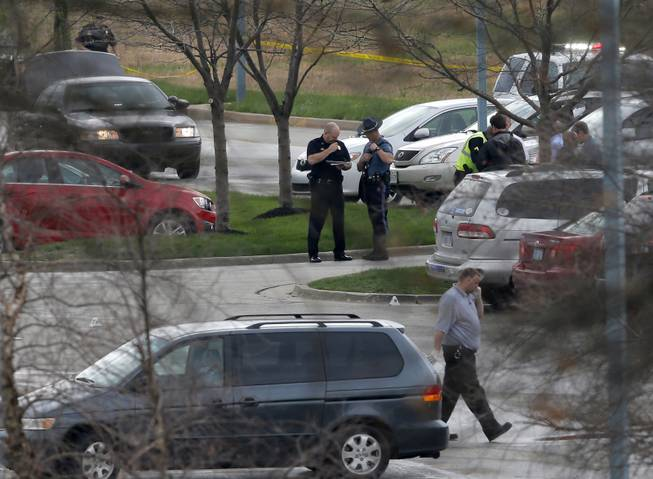 Investigators work behind a police line near the location of a shooting at the Jewish Community Center in Overland Park, Kan., Sunday, April 13, 2014.
