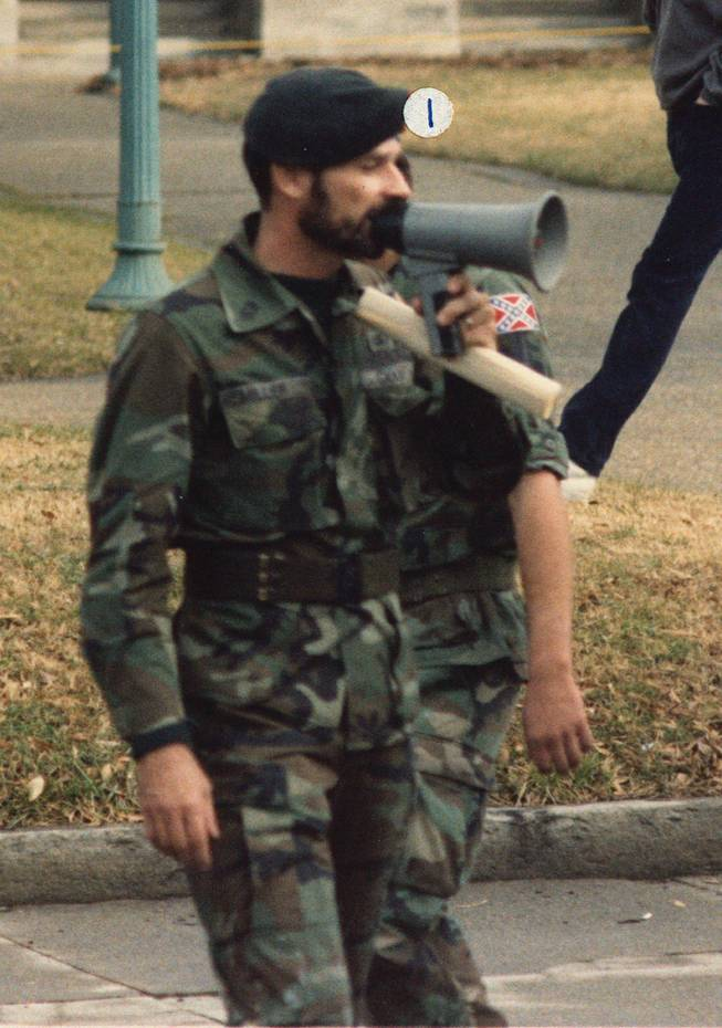 In this Jan. 18, 1986 photo released by Southern Poverty Law Center shows Frazier Glenn Cross, also known as Frazier Glenn Miller, at a Martin Luther King holiday protest in Raleigh, N.C. Cross, 73, accused of killing three people in attacks at a Jewish community center and Jewish retirement complex near Kansas City on Sunday, April 13, 2014, is a known white supremacist and former Ku Klux Klan leader who was once the subject of a nationwide manhunt. He was booked into Johnson County jail on a preliminary charge of first-degree murder. The identifier label above Cross' head was placed by the source.