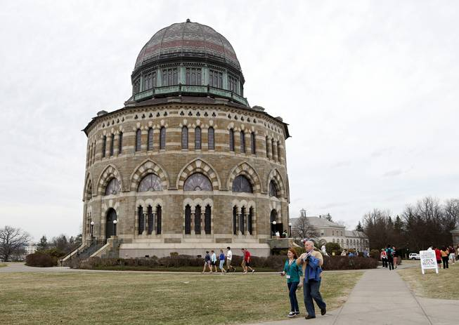 People walk by the Nott Memorial at Union College on Monday, April 14, 2014, in Schenectady, N.Y. Tiny Union, enrollment 2,200, defeated Minnesota, enrollment 48,000, Saturday for its first NCAA hockey title.
