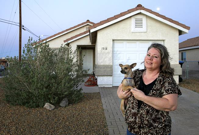 Liz Epperson poses with her dog Mi Corazon, a four-year-old chihuahua, in front of her home in Henderson Sunday, April 13, 2014. Epperson put 450 hours of sweat equity into the house which was built in 1997, she said.