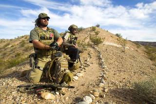 Reid Hendricks of Camden, Tenn., and Jim (no last name provided) of Las Vegas take up a position on a hill by Cliven Bundy's ranch near Bunkerville on Tuesday, April 15, 2014. Hendricks is a former Marine (honorably discharged) and has worked as a police officer and a high school history teacher, he said.