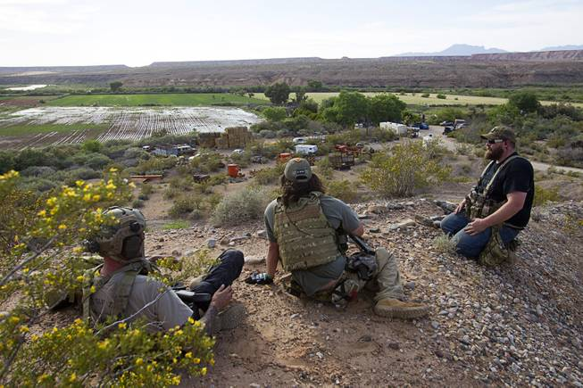 Jim (no last name provided) of Las Vegas, Reid Hendricks, center, of Camden, Tenn. and Ian Houston of Eugene, Ore.  take up a position on a hill by Cliven Bundy's ranch near Bunkerville Tuesday, April 15, 2014. Hendricks is a former Marine (honorably discharged), and has worked as a police officer and a high school history teacher, he said.