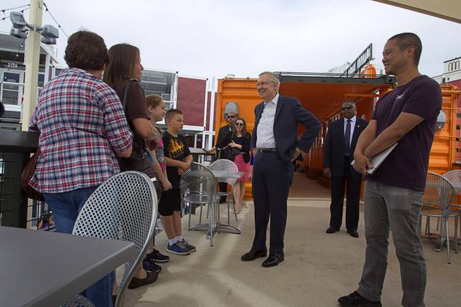 Senate Majority Leader Harry Reid (D-NV) stops to talk with the Stephens family of Henderson during downtown Las Vegas tour with Zappos CEO Tony Hsieh at Las Vegas Container Park Tuesday, April 15, 2014.
