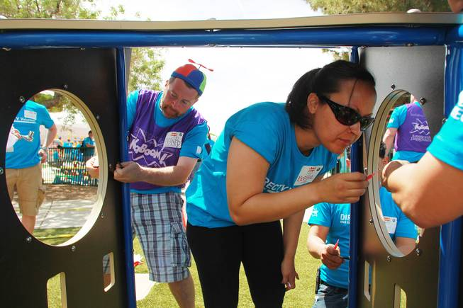 Kevin Nelson and Kristal Jacobs assemble a section of a play structure as volunteers work on building a KaBoom playground for Child Haven Tuesday, April 15, 2014. Clark County Department of Family Services and Chicanos Por La Causa teamed up with volunteers from DirectTV and local businesses to rebuild the playground that was closed in 2012.