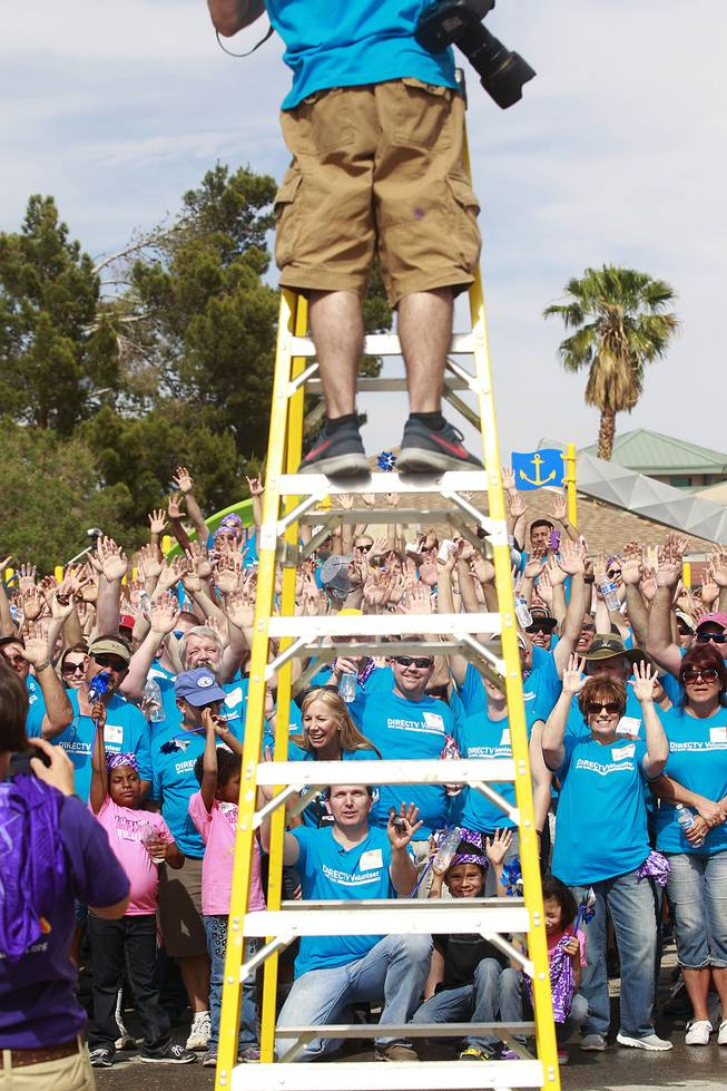 Volunteers cheer while having their photo taken after building a KaBoom playground for Child Haven Tuesday, April 15, 2014. Clark County Department of Family Services and Chicanos Por La Causa teamed up with volunteers from DirectTV and local businesses to rebuild the playground that was closed in 2012.