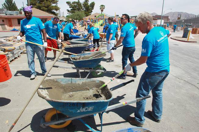 Volunteers mix cement as they work on building a KaBoom playground for Child Haven Tuesday, April 15, 2014. Clark County Department of Family Services and Chicanos Por La Causa teamed up with volunteers from DirectTV and local businesses to rebuild the playground that was closed in 2012.