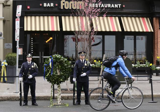 A Boston Police honor guard is posted outside the Forum restaurant, the site of the second of two bombs that exploded near the finish line of the 2013 Boston Marathon, Tuesday, April 15, 2014 in Boston. Three were killed and more than 260 injured in last year's explosions near the finish line of the race.