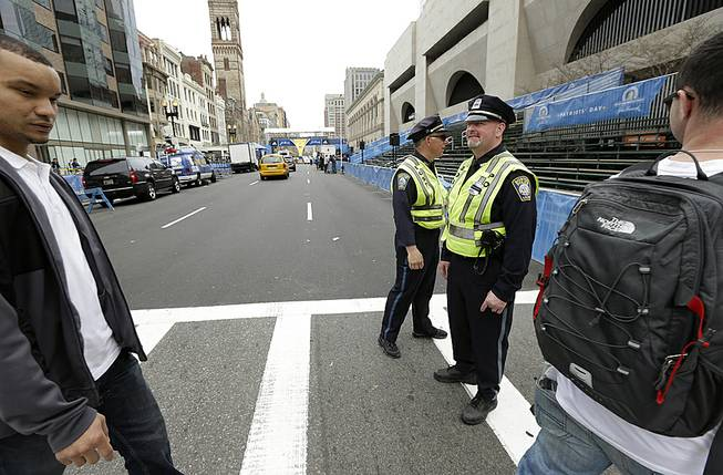 Boston Police, center, stand near the finish line of the Boston Marathon, behind, on Boylston Street, Monday, April 14, 2014, in Boston.