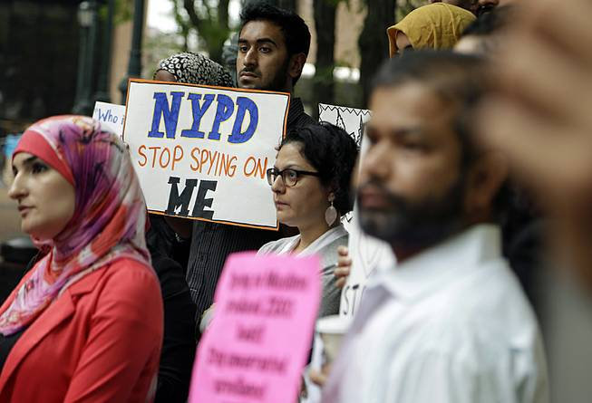 A group of people holds signs protesting the New York Police Department's program of infiltrating and informing on Muslim communities during a rally near police headquarters in New York, Aug. 28, 2013.