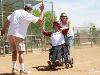 Ben Dauterive from the Loan Writers gets a high five as his mom Kim Dauterive helps him across home plate as Silverado Little League hosts Challenger Little League day Saturday, April 12, 2014.
