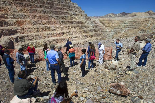 Teachers listen to Barrick's Tim Buchanan, at fence post, at the new Bullfrog Mine near Beatty during the 25th Annual Southern Nevada Earth Science Education Workshop Wednesday, April 16, 2014. The gold and silver mine was in operation from 1988 to 1999. The tour also included a trip the ghost town of Rhyolite. Teachers spent the first day of the workshop focused on classroom activities related to rocks and minerals.