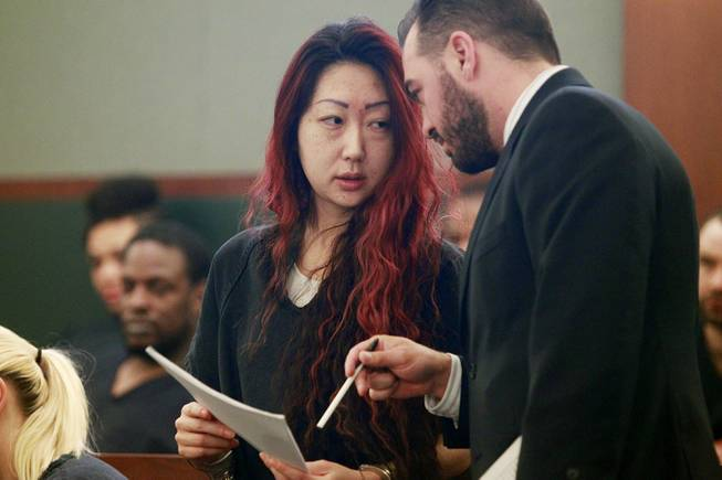 Gloria Lee speaks with attorney Dustin Marcello as she appears in Clark County District Court for her arraignment on charges stemming from an arson fire at Lee's pet store Wednesday, April 16, 2014.