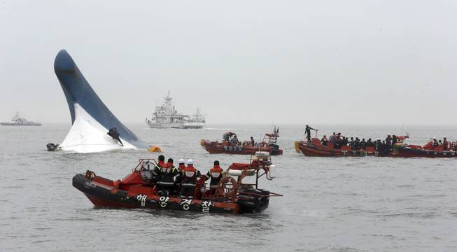 South Korean coast guard officers try to rescue passengers from ferry Sewol in the water off the southern coast near Jindo, south of Seoul, South Korea, Wednesday, April 16, 2014. Dozens of boats, helicopters and divers scrambled Wednesday to rescue more than 470 people, including 325 high school students on a school trip, after the ferry sank off South Korea's southern coast.
