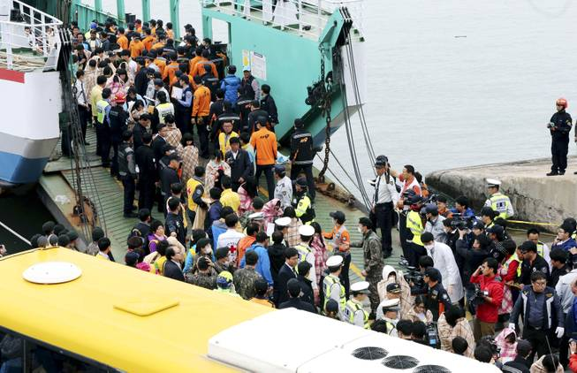 Rescued passengers are escorted by members of a rescue team upon their arrival at a port in Jindo, south of Seoul, South Korea, Wednesday, April 16, 2014. More than 100 people were still unaccounted Wednesday several hours after a ferry carrying 476, most of them high school students, sank in cold waters off South Korea's southern coast, killing at least two and injuring 14, officials said.