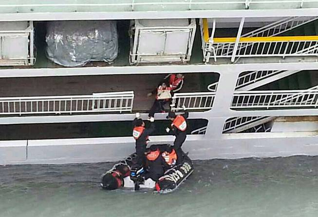 In this photo released by the South Korean Coast Guard via Yonhap News Agency, South Korean coast guard officers rescue passengers from a sinking ferry off the southern coast near Jindo, south of Seoul, South Korea, Wednesday, April 16, 2014. A ferry carrying 459 people, mostly high school students on an overnight trip to a tourist island, sank off South Korea's southern coast on Wednesday, leaving nearly 300 people missing despite a frantic, hours-long rescue by dozens of ships and helicopters.