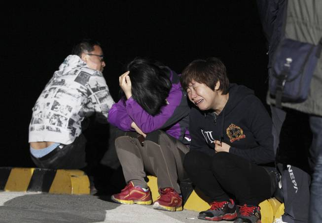 A relative weeps as she waits for missing passengers of a sunken ferry at Jindo port, South Korea, Wednesday, April 16, 2014. The ferry carrying 459 people, mostly high school students on an overnight trip to a tourist island, sank off South Korea's southern coast on Wednesday, leaving nearly 300 people missing despite a frantic, hours-long rescue by dozens of ships and helicopters.