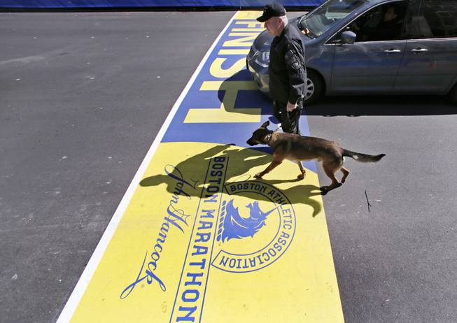 Boston Police Officer John Quinn walks with, Miller, his bomb-detection canine, over the finish line while sweeping the area in preparation for the Boston Marathon, Wednesday, April 16, 2014.