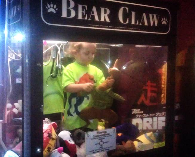 In this April 14, 2014, photo provided by Rachelle Hildreth, a 3-year-old boy plays with stuffed toys inside a claw crane game machine at a bowling alley in Lincoln, Neb.
