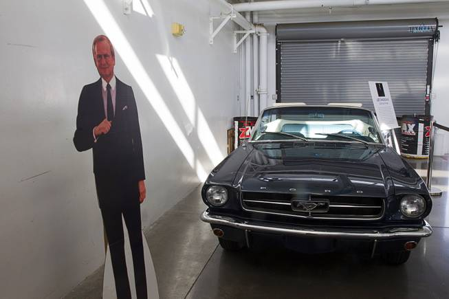 A cardboard cutout of automotive executive Lee Iacocca is shown by his 1965 Mustang convertible during the Mustang 50th Birthday Celebration at the Las Vegas Motor Speedway Thursday April 17, 2014. Iacocca participated in the design of the Ford Mustang and other successful Ford models before joining Chrysler.