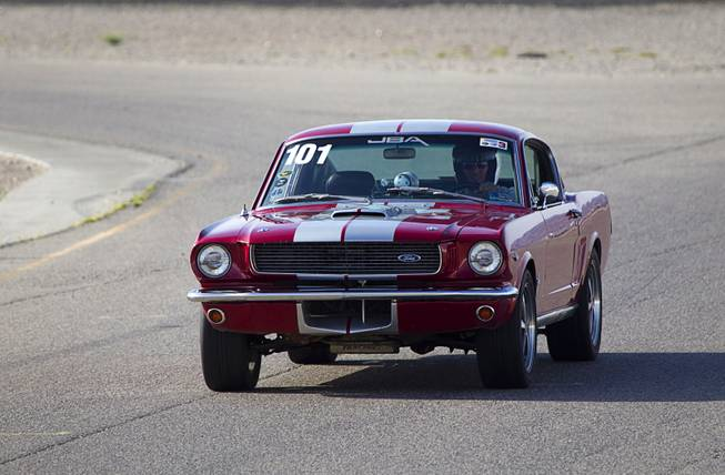 A 1966 Ford Mustang fastback is driven on a road course during the Mustang 50th Birthday Celebration at the Las Vegas Motor Speedway Thursday April 17, 2014.
